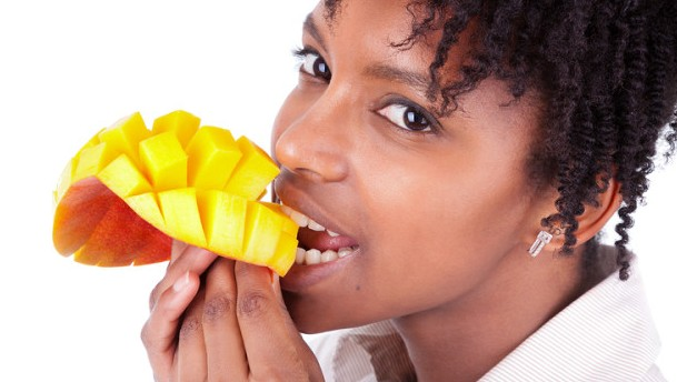 Young happy black / african american woman eating fresh mango isolated on white background